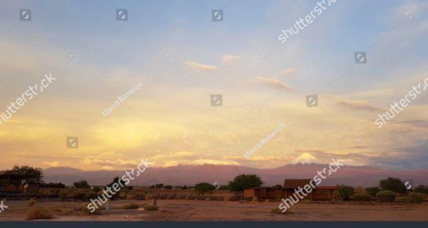Las luces del atardecer en el paisaje árido y desolado del desierto de Atacama con los picos de los volcanes nevados de la cordillera de los Andes en el fondo. Autor y Copyright Marco Ramerini