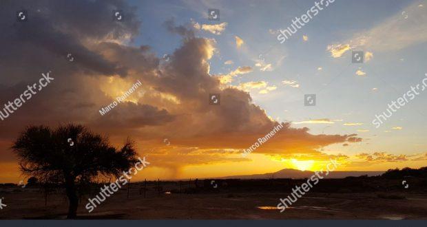 Puesta de sol con árbol solitario y tormenta formando en la distancia en las tierras áridas del desierto de Atacama, Chile. Autor y Copyright Marco Ramerini